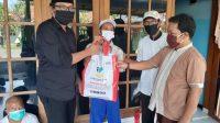 foto : Ketua DPRD Banyuwangi menyerahkan bantuan sembako dari kemensos pada warga (Abi beritalima.com)