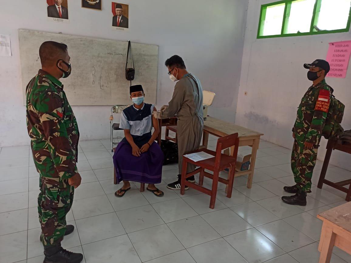 Aparat TNI mendampingi proses vaksinasi di Pondok Pesantren Mambaul Ulum Bondowoso. (Rois/beritalima.com)